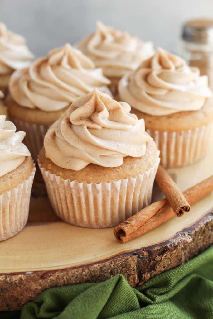 Snickerdoodle Cupcakes on a wood slice with cinnamon sticks next to it
