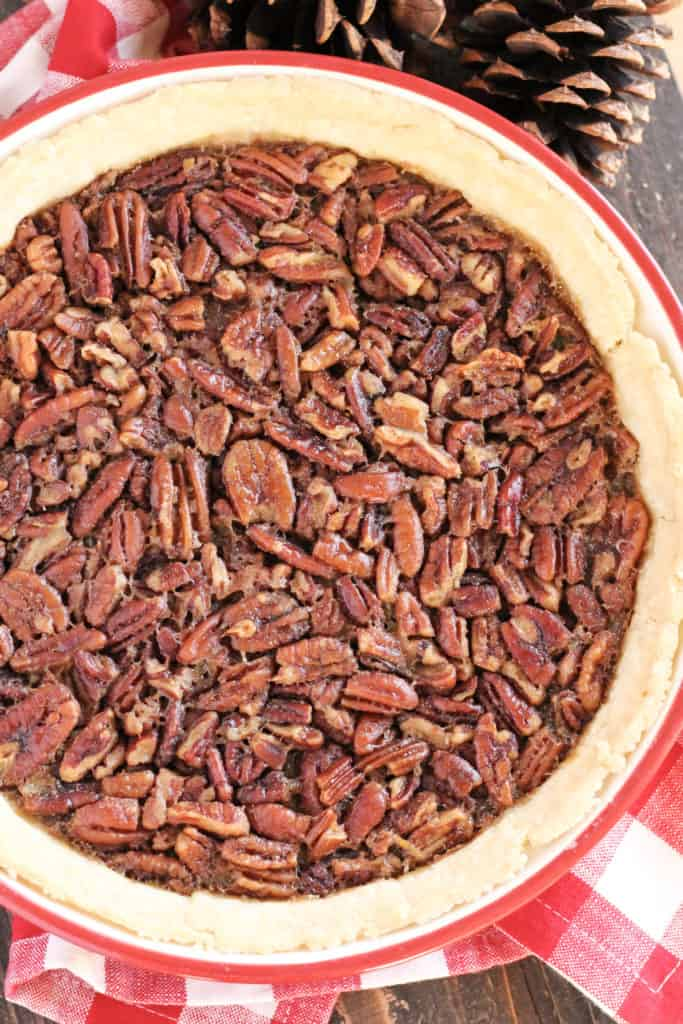 A pie dish with pecan pie inside