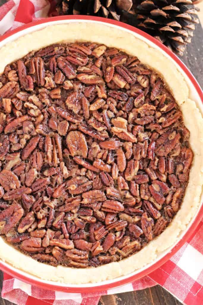 A pie dish with pecan pie inside