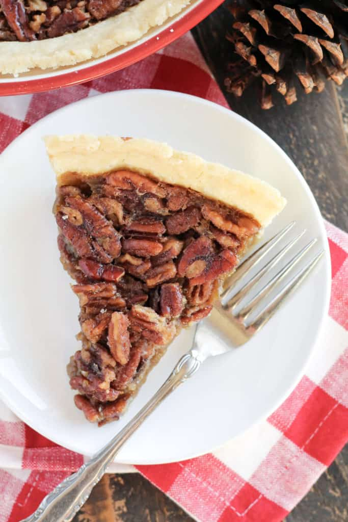 A slice of pecan pie from overhead, on a plate, with a fork