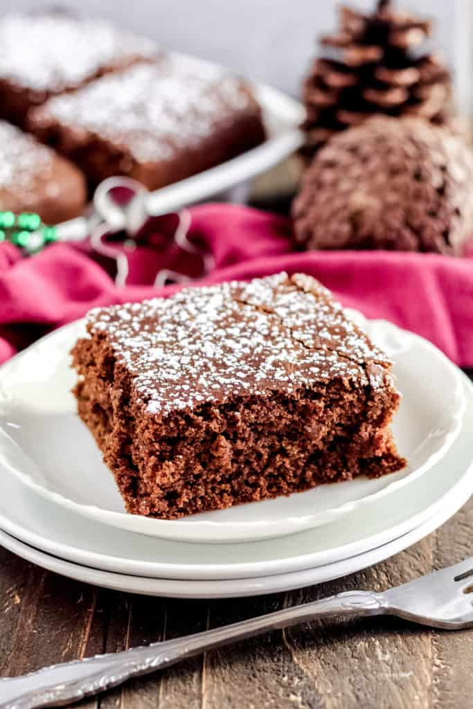 One piece of Gingerbread Cake on three plates, with a fork in front