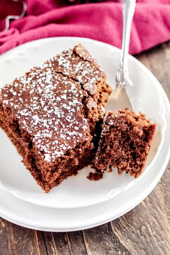 A top down view of one piece of Gingerbread Cake with a fork holding one bite cut off of it