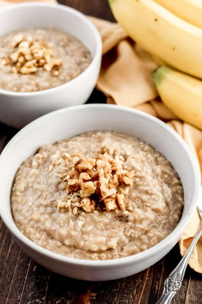 two bowls of Banana Steel Cut Oats with walnuts sprinkled on top