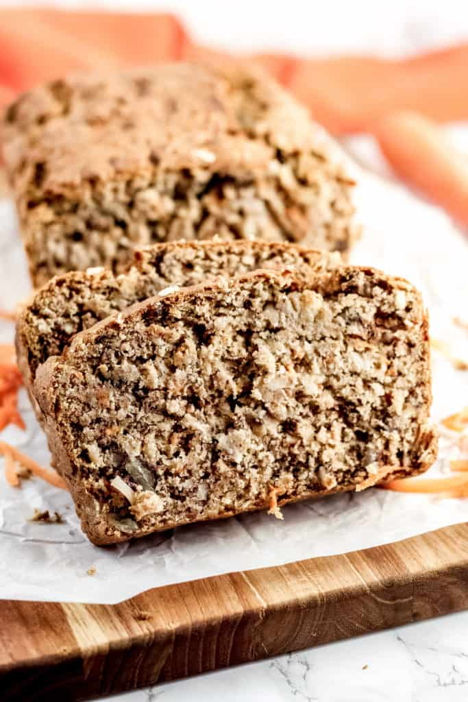 Two slices of Carrot Cake Banana Bread  in front of the loaf, on a wood cutting board