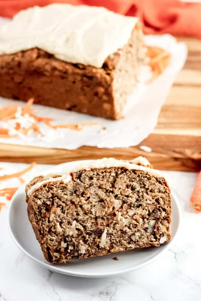 a plate with two slices of Carrot Cake Banana Bread, with the loaf behind on a wood cutting board