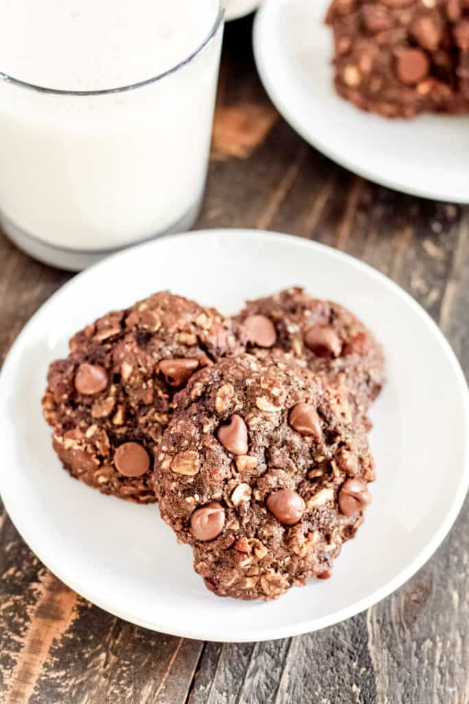 a plate of three Chocolate Breakfast Cookies with a glass of milk behind