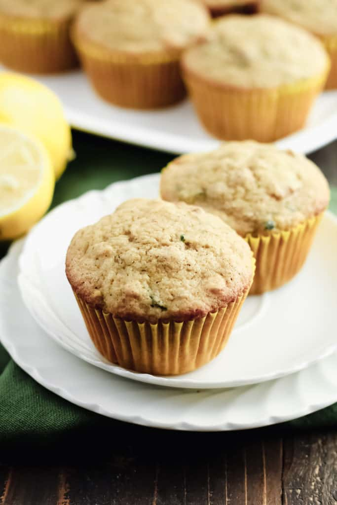 two Lemon Zucchini Oat Muffins on two plates, with a tray of more muffins behind