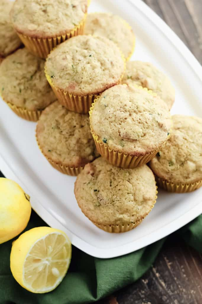 Lemon Zucchini Oat Muffins stacked on a tray with lemons next to the tray