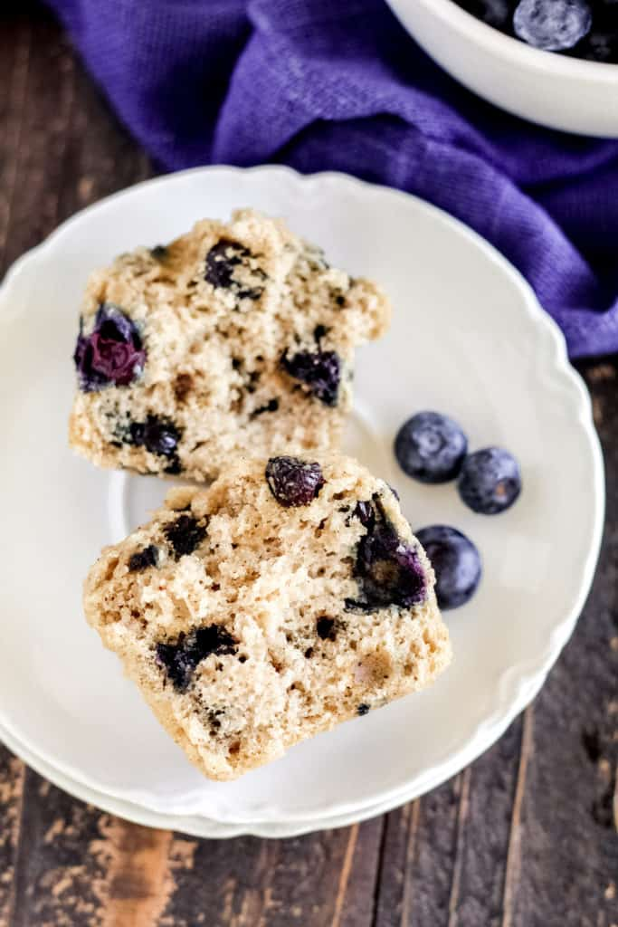 a blueberry muffin cu tin half on a plate, with blueberries.