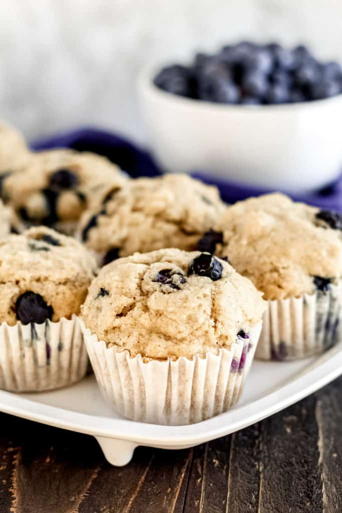 a tray of blueberry muffins with a bowl of blueberries behind