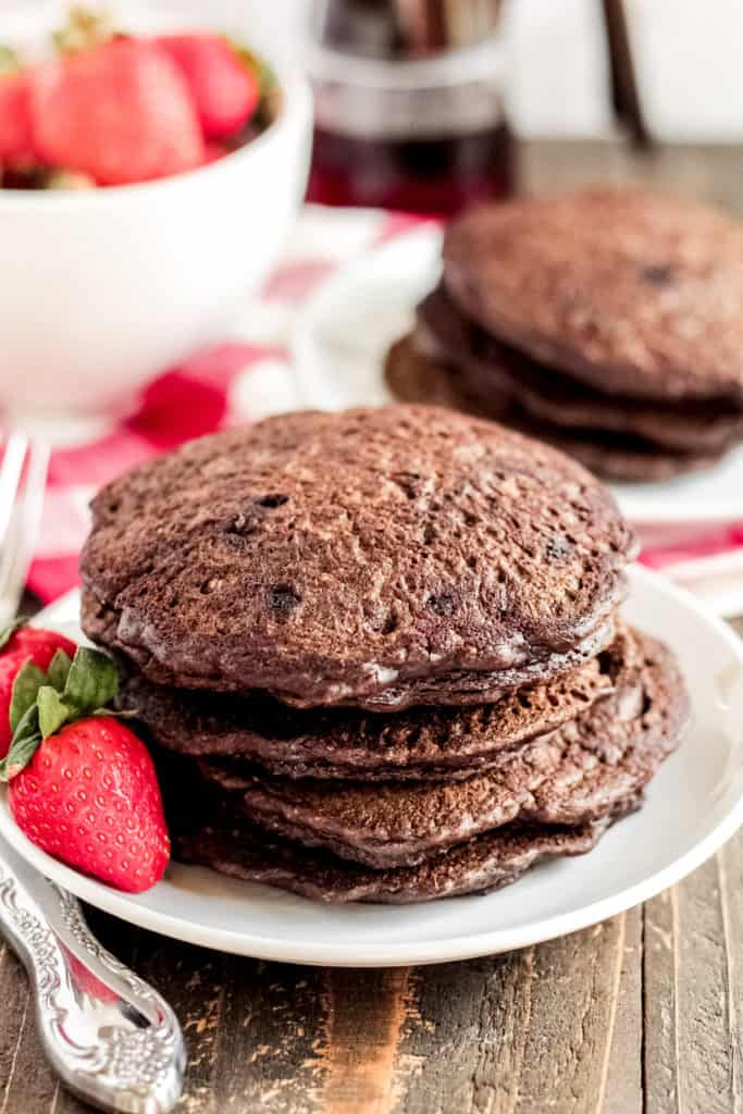 Stack of chocolate oat pancakes on a plate with a strawberry