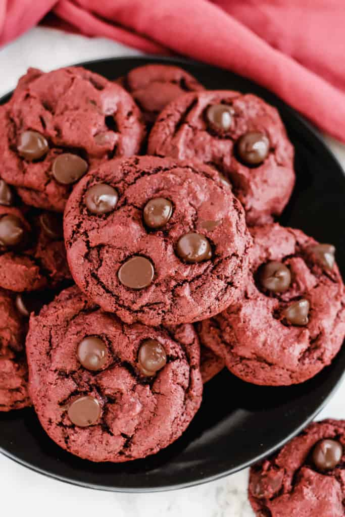 a black plate filled with Red Velvet Chocolate Chip Cookies