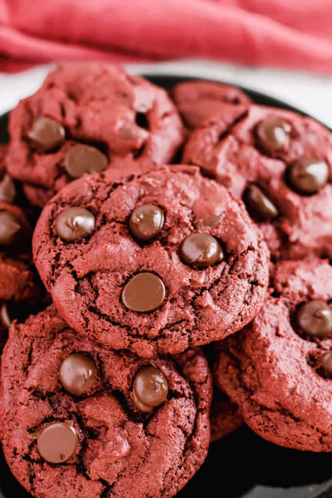 close up of one Red Velvet Chocolate Chip Cookie on a plate filled with cookies