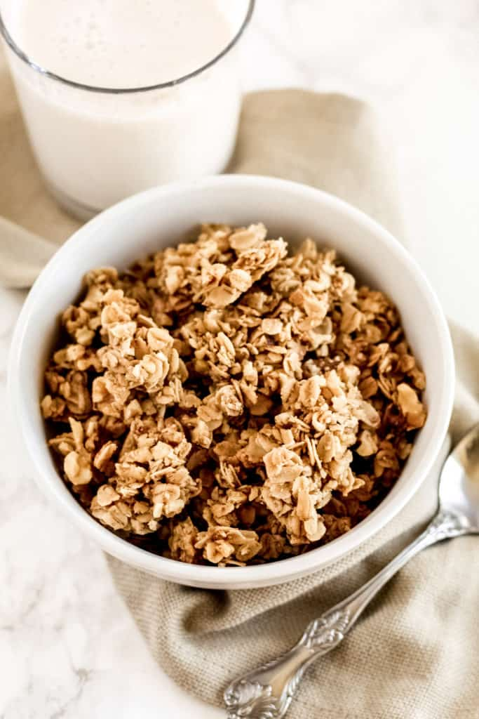 a bowl of vanilla granola with a cup of milk behind and a spoon.