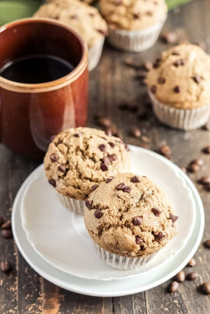 two muffins on two plates.