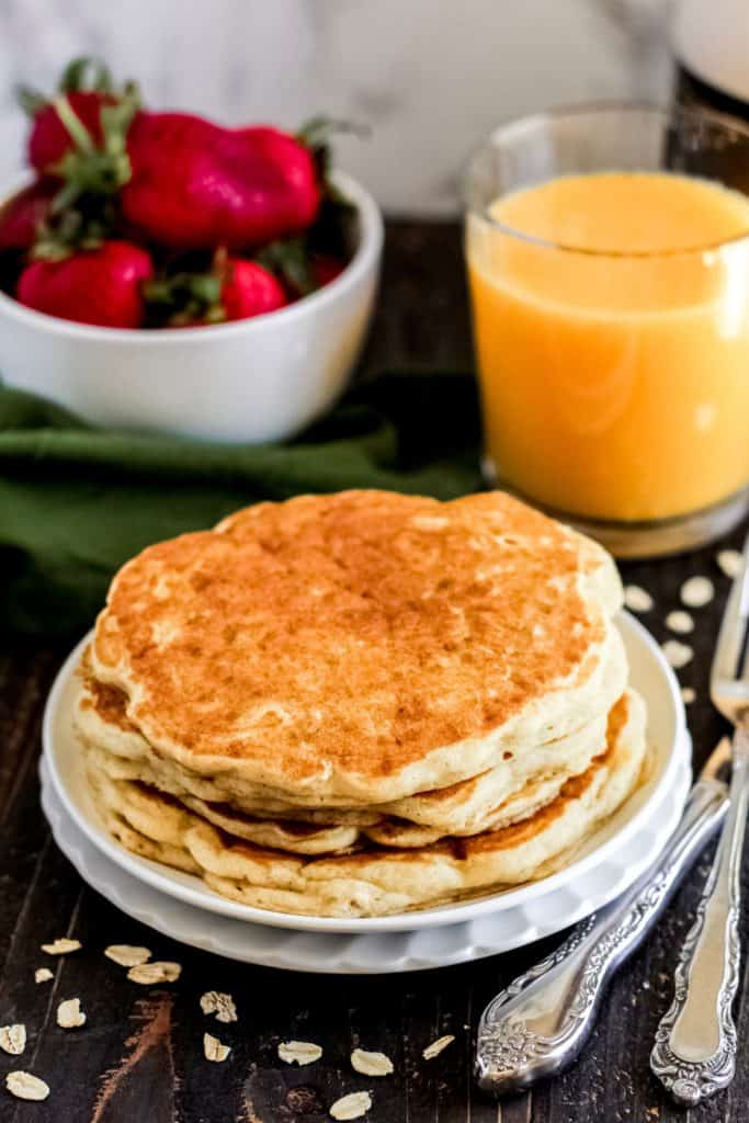 stack of pancakes with oats sprinkled around.