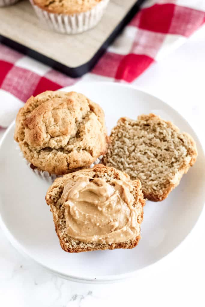 muffins on a plate with peanut butter spread on top of one cut open