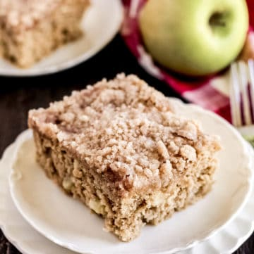 A close up of a piece of cake on a plate, with Apple and Cinnamon