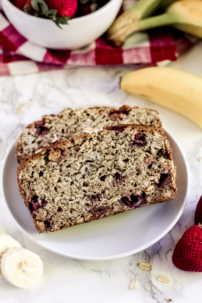 two pieces of strawberry banana oatmeal bread on a plate