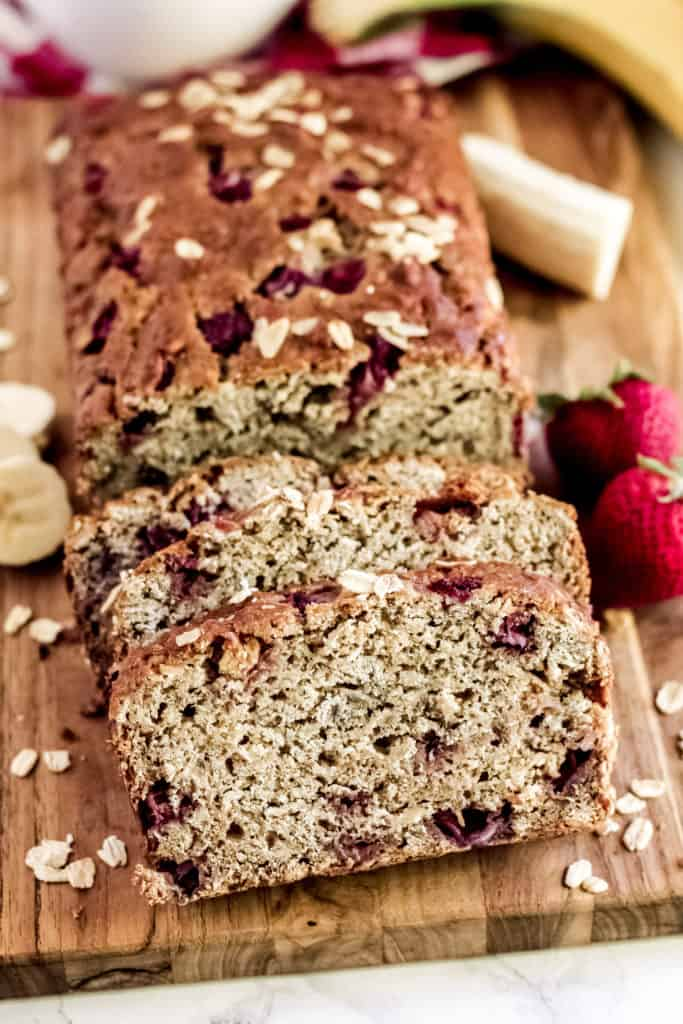 a loaf of strawberry banana oatmeal bread on a wood cutting board sliced up