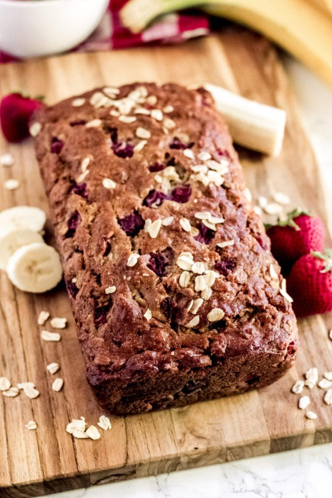 a loaf of strawberry banana oatmeal bread on a wood cutting board.