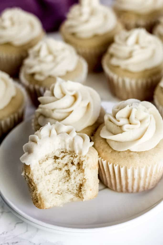 a plate with three vanilla cupcakes, with one with a bite taken out of it