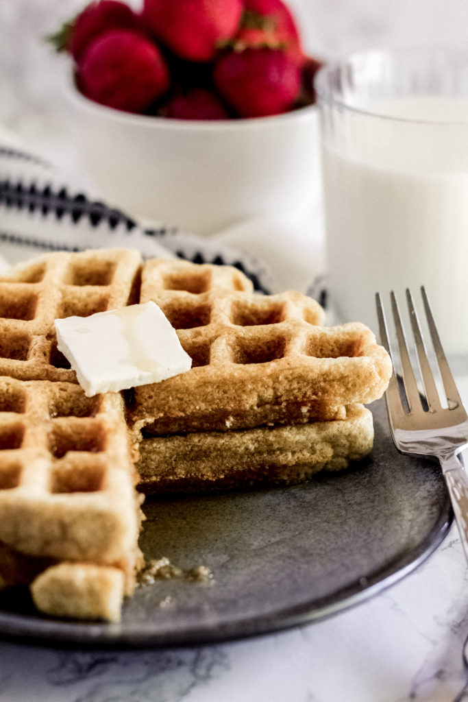 Two Healthy Oat Waffles stacked on top of each other on a plate with butter on top, and 1/4 removed, to see the inside