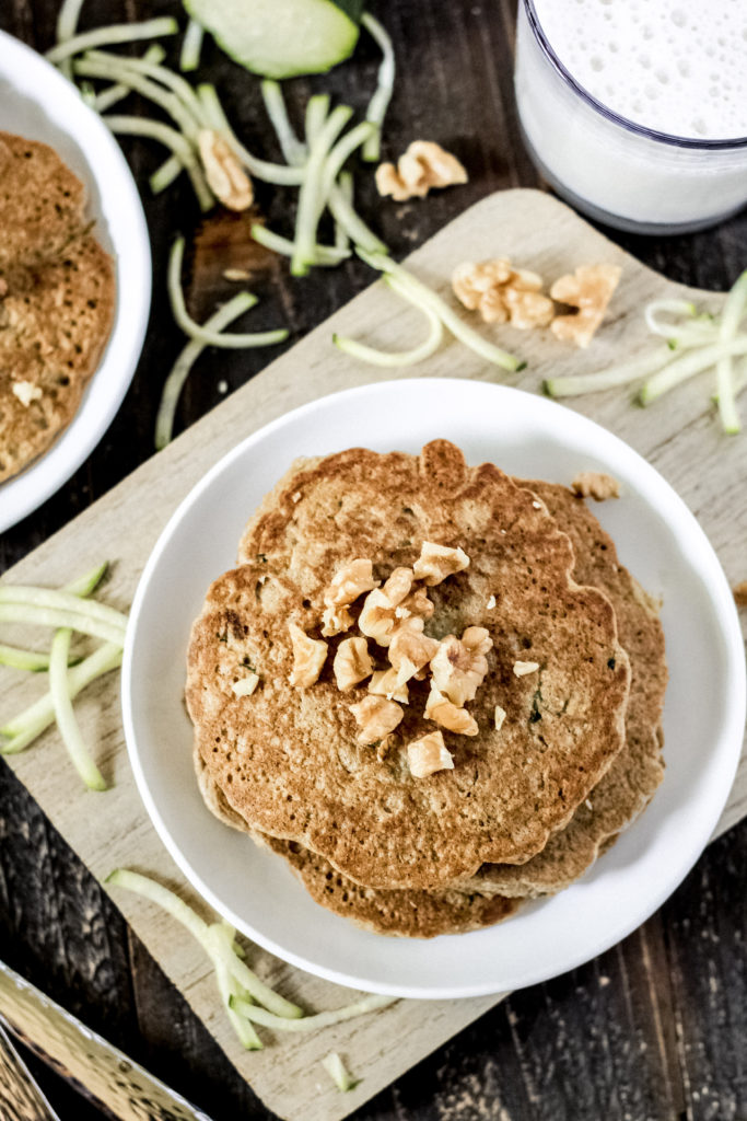 Top down view of a stack of pancakes on a plate with walnuts on top, with shredded zucchini sprinkled around.