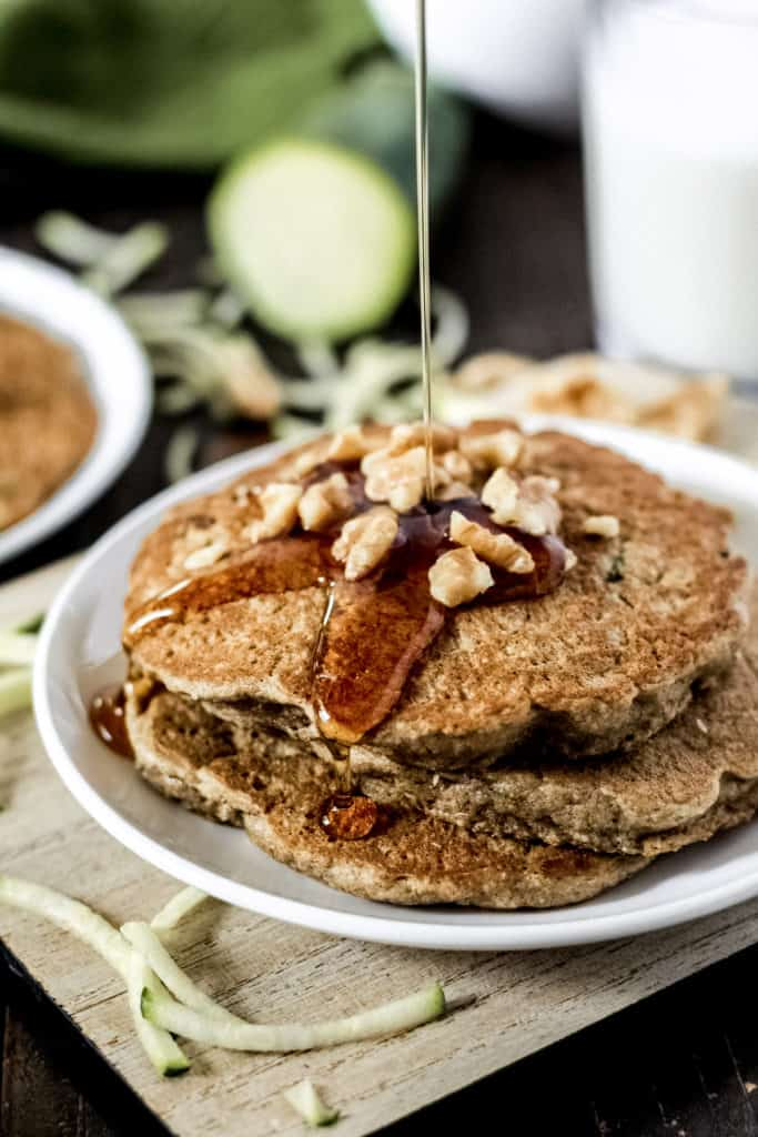 A stack of zucchini oat pancakes with walnuts on top and maple syrup being poured on top.