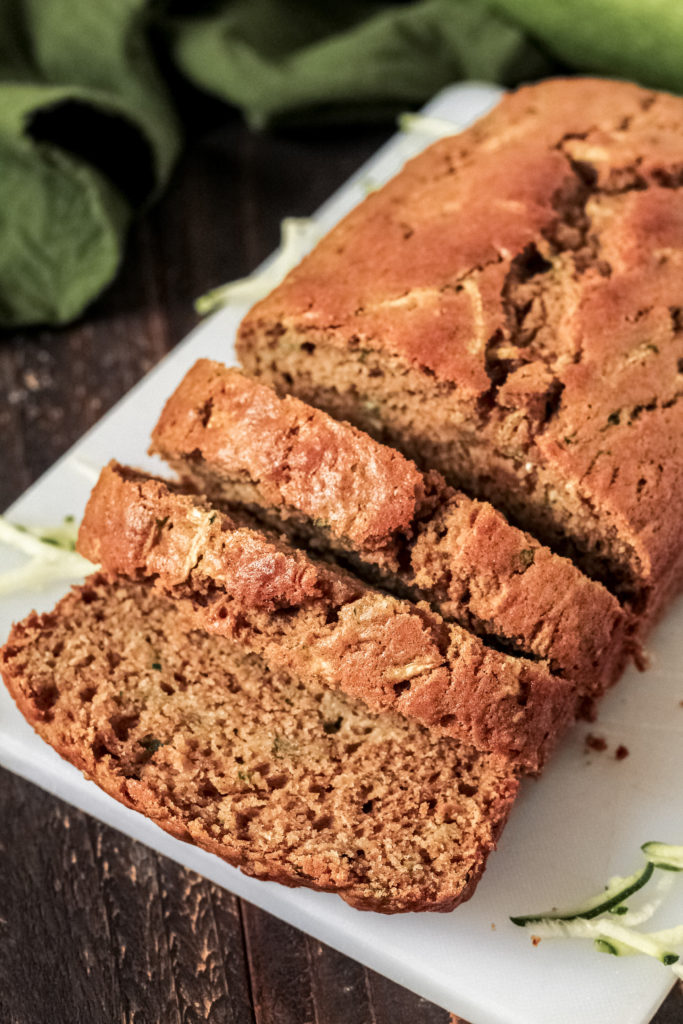 Close up view of a loaf of zucchini bread on a cutting board, with a few slices cut out of the front