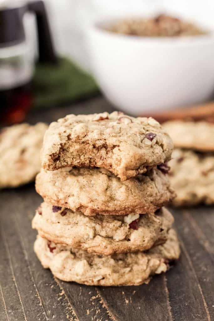 A stack of maple pecan oatmeal cookies with a bite taken out of the top cookie