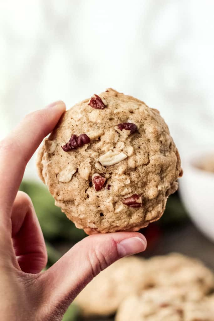One maple pecan oatmeal cookie held up between two fingers