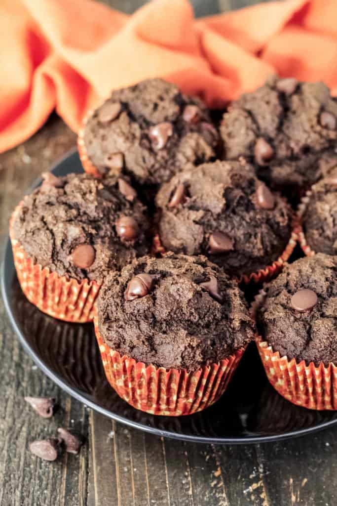 A black plate filled with double chocolate pumpkin oat muffins
