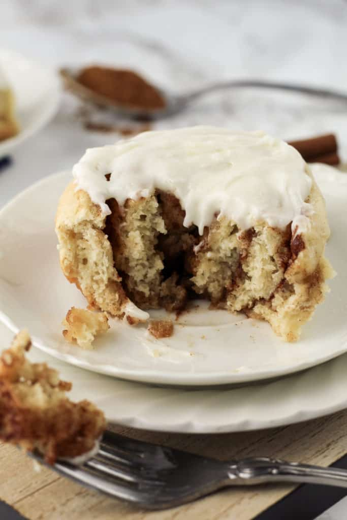 A frosted cinnamon roll on a plate